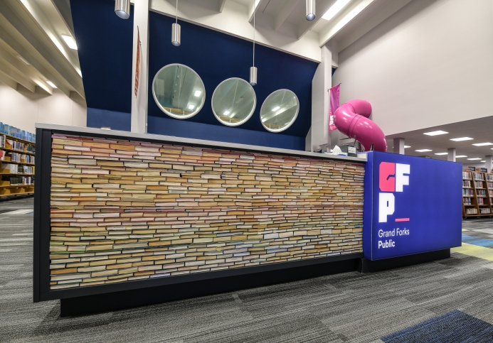 """The front desk and giant pink slide, bringing our """"playground for curious minds"""" to life."""
